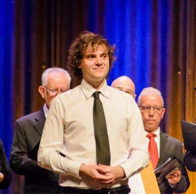 Foto colorida dp maestro Miguel Philippi, em uma apresentação no palco.